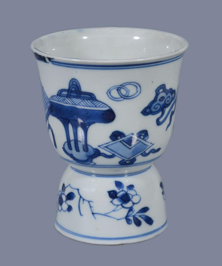 A Chinese blue and white stem cup, Kangxi, painted with precious objects