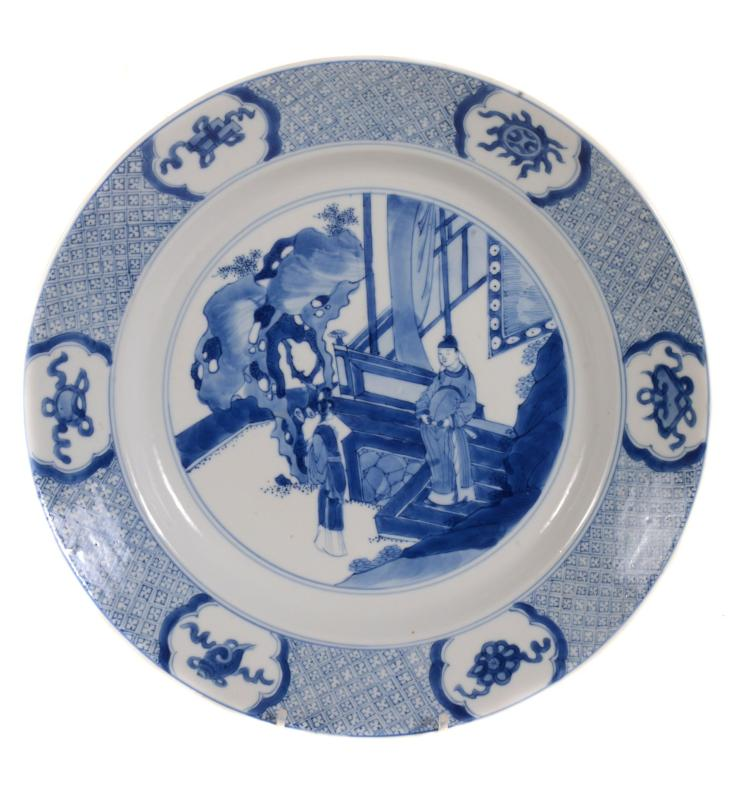 A Chinese blue and white plate, Kangxi, with diaper pattern border with six...