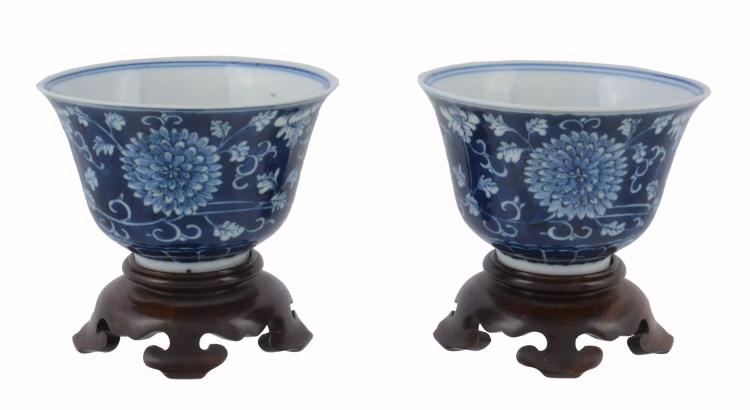 A pair of Chinese blue and white bowls, each painted with flowering...