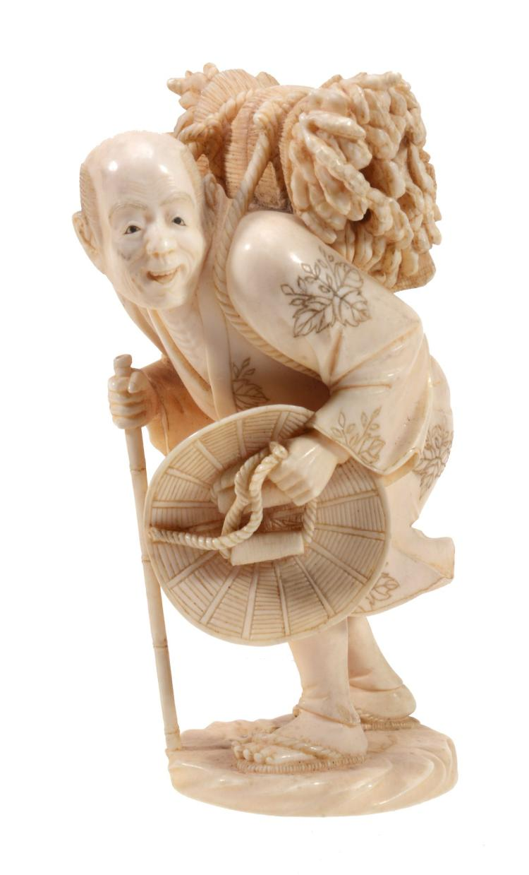 A Japanese Ivory Okimono of a woodsman on a shaped base