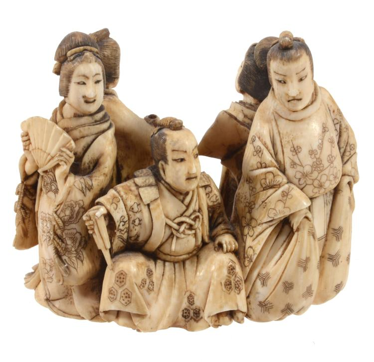 An Ivory Okimono depicting a seated nobleman surrounded by two courtiers and...