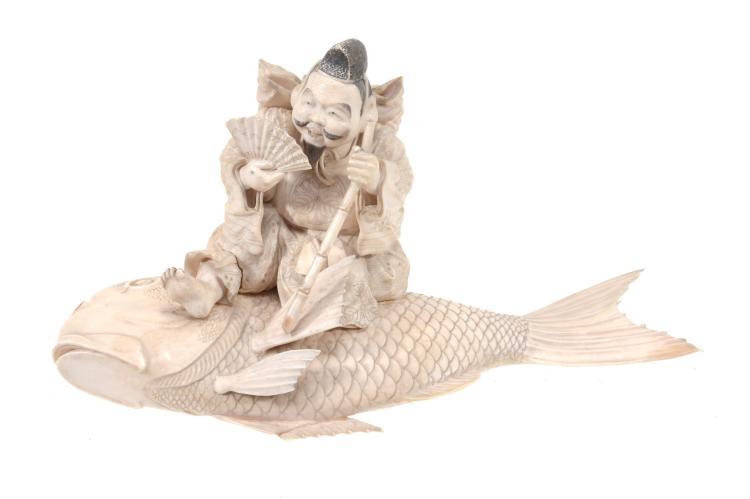 A Japanese Ivory Okimono of Ebisu, the smiling deity holding a bamboo staff...