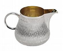 A silver cream jug by Gerald Benney, London 1988,