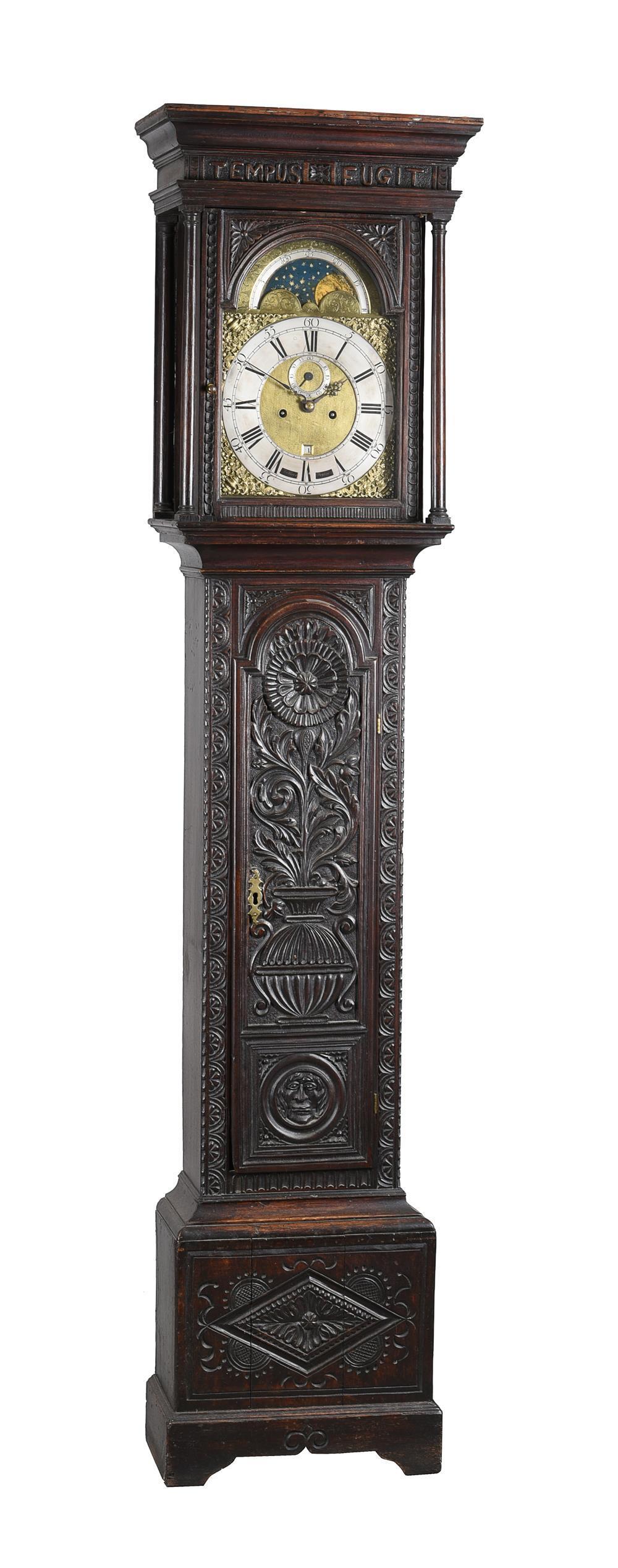 A carved oak longcase clock