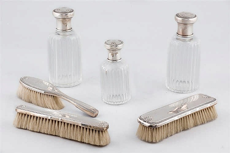 A glass and silver vanity set