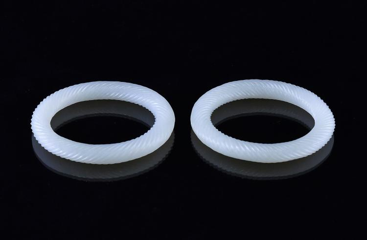 A FINE PAIR OF ROPE PATTERNED WHITE JADE BANGLES