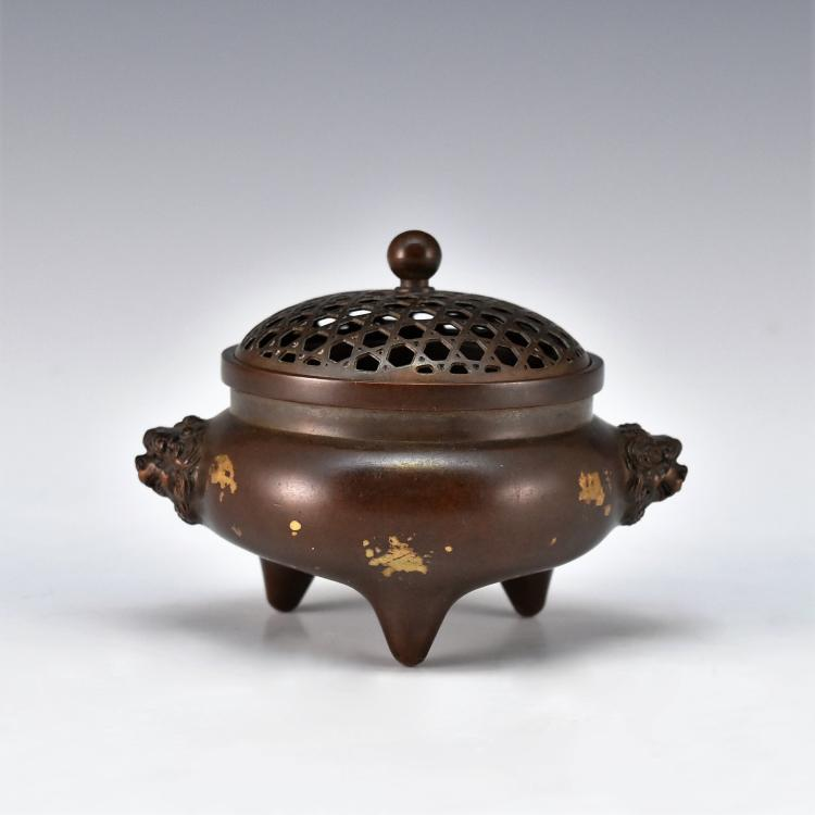 A CHINESE BRONZE TRIPOD COVERED CENSER WITH GILT ACCENTS