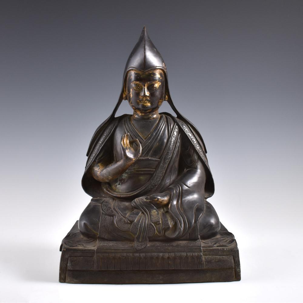 "A 12"" SINO-TIBETAN GILT-BRONZE FIGURE OF A LAMA"