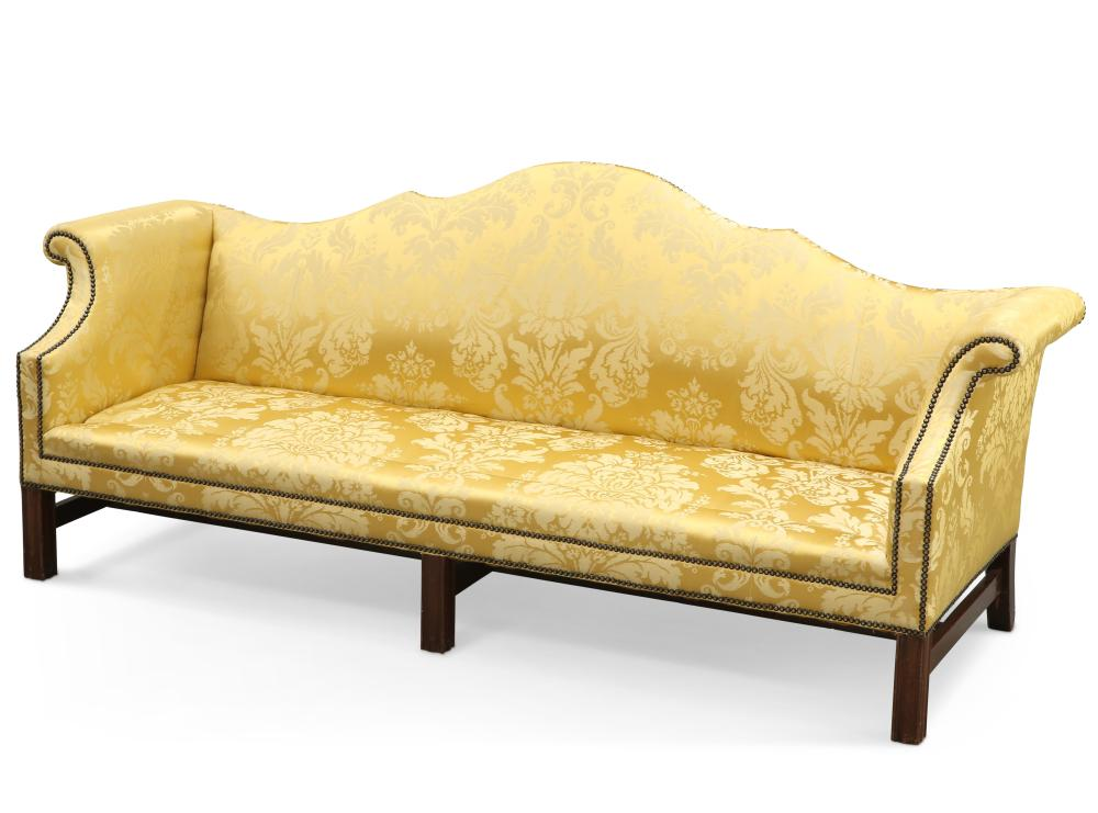 A GEORGE III STYLE MAHOGANY AND UPHOLSTERED SETTEE, with out-scrolled arms