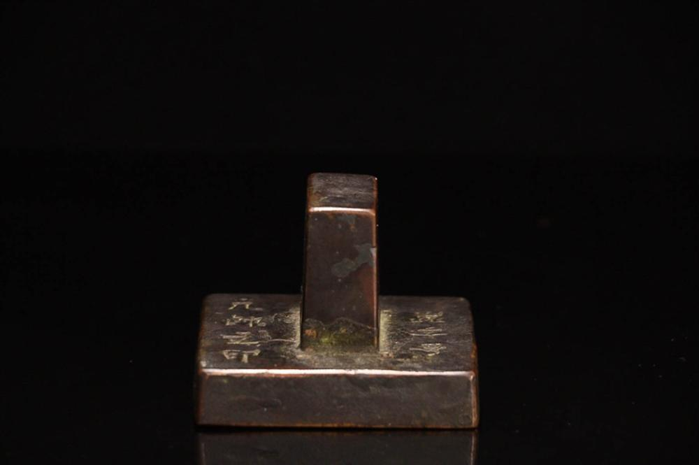 A BRONZE SQUARE SHAPED SEAL