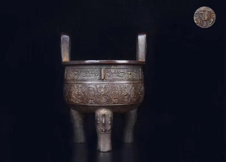 A BRONZE ARCHIZE PATTERN TRIPOD WITH DOUBLE EARS