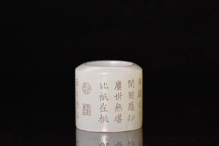 A QING DYNASTY HETIAN WHITE THUMB RING WITH LANDSCAPE AND POEM