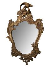 A curvaceous Italian rococo style cartouche shaped carved gilt wood mirror