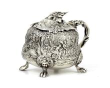 An exceptional George IV Sterling Silver Teniers style mustard or honey pot by Edward Farrell, London 1821. Of squat, pear form with high relief embossed decoration depicting traditional Dutch scenes with figures and animals among foliate scrolls and trees. The piece sits on four lion's paw feet with maiden's face mask decoration, and the handle is modeled in the trompe l'oeil manner as a scrolling branch with vines. The hinged lid features further chased decoration including foliage and scrolls, and is surmounted by a cast and applied flower branch finial with a bee resting atop it. Length (incl handle) 11.5cm / 4.5