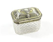 An antique Georgian Sterling Silver gilt lidded cut glass tea caddy marked with lion passant and maker's mark (indecipherable) only. The octagonal cut glass body with silver gilt mount and hinged lid, featuring high relief chased decoration depicting rocaille foliage and scrolls, within bound reeded borders. Diameter 12cm / 4.75