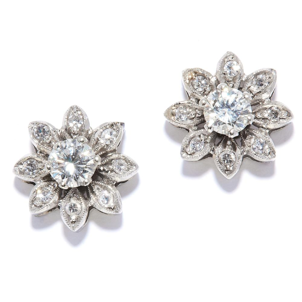 A PAIR OF DIAMOND CLUSTER STUD EARRINGS in 14ct white gold, each depicting a flower set with round cut diamonds, stamped 14KT, 1.0cm, 3.4g.