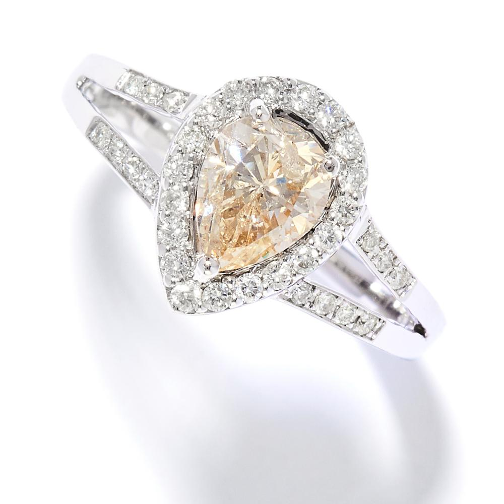 1.01 CARAT DIAMOND DRESS RING in 18ct white gold, comprising of a pear cut diamond of approximately 1.02 carats in a border of round cut diamonds totalling approximately 0.21 carats, stamped 750, size N / 6.5, 3.64g.