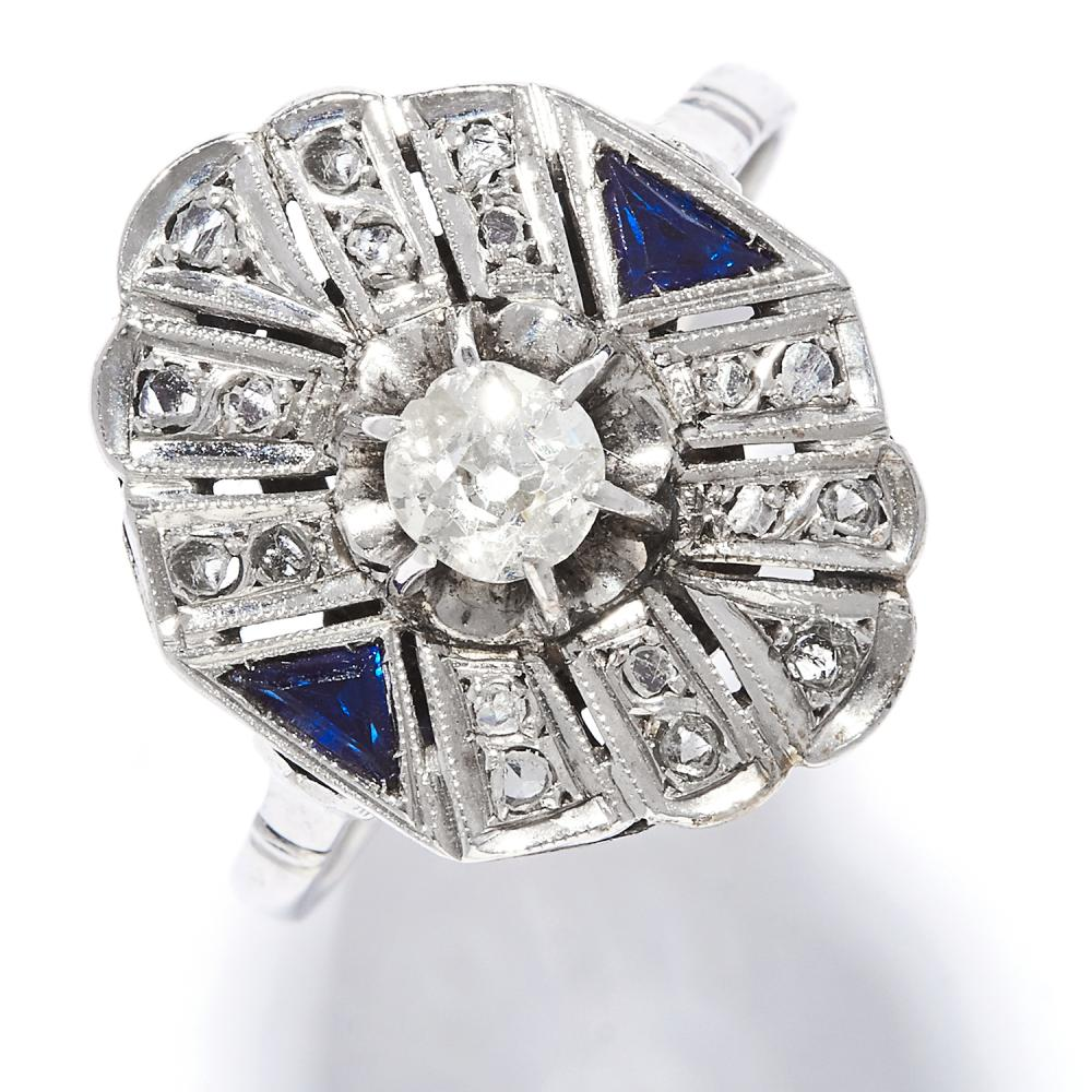 ART DECO DIAMOND AND SAPPHIRE RING in platinum or white gold, the oval face set with an old cut diamond between step cut sapphires and further round cut diamonds, unmarked, size Q / 8, 4.0g.