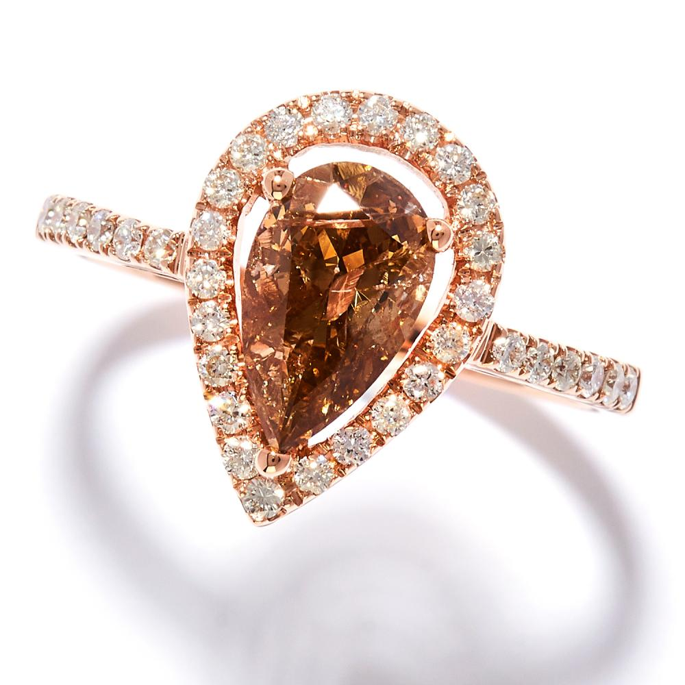 1.08 CARAT FANCY BROWN DIAMOND DRESS RING in 18ct rose gold, set with a pear cut brown diamond of approximately 1.08 carats in a border of round cut diamonds, stamped 750, size N / 7, 2.74g.