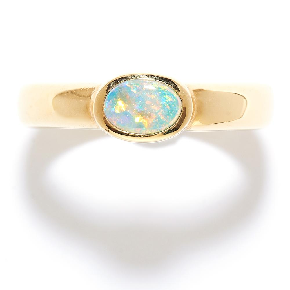 OPAL DRESS RING, 1970s in 18ct yellow gold, the oval cabochon opal within a stylised band, stamped 750, size S / 9, 11.9g.