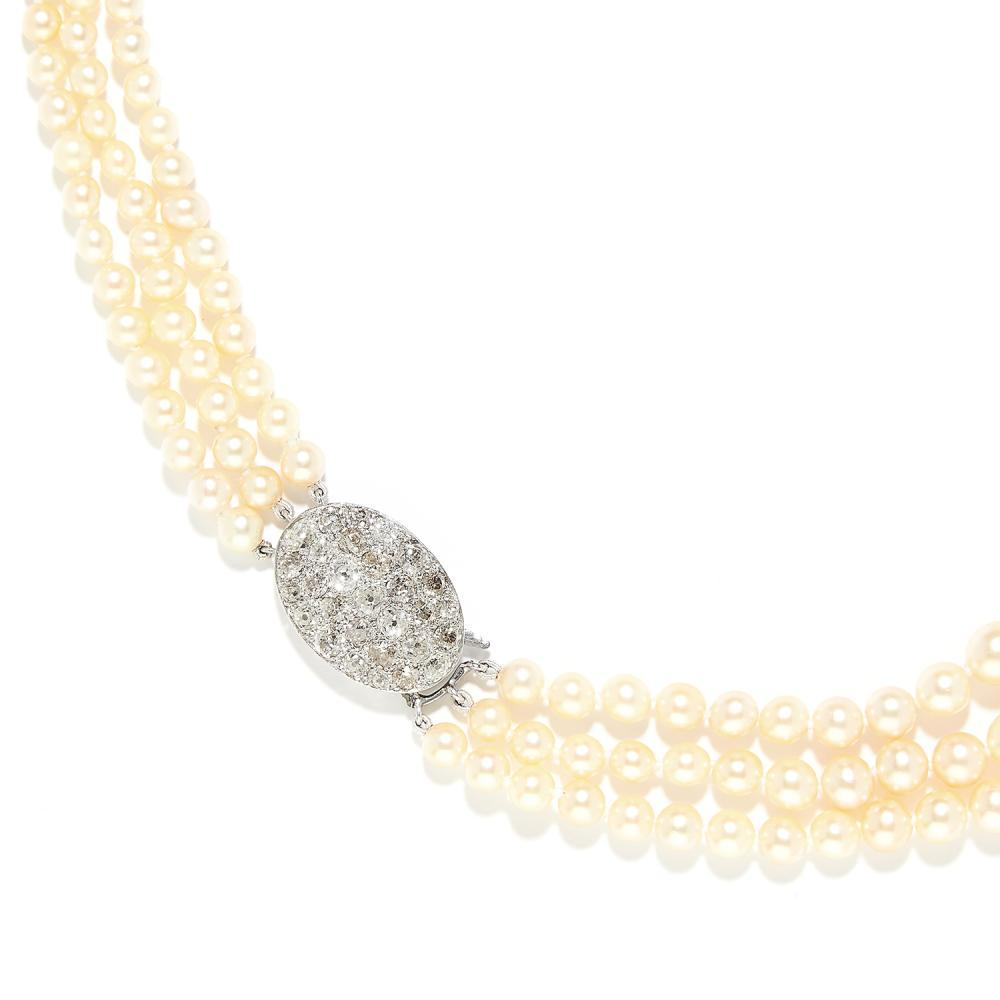 THREE ROW PEARL AND DIAMOND NECKLACE in white gold or platinum, comprising three rows of graduated pearls up to 7.4mm, on an oval clasp jewelled with old cut diamonds totalling 2.5-3.0 carats, unmarked, 41.0cm, 41.9g.