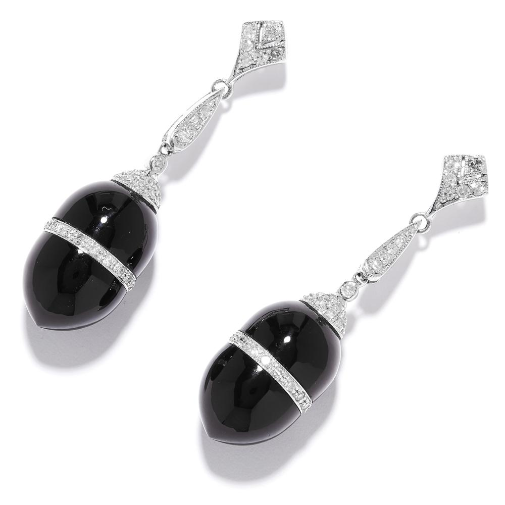 ONYX AND DIAMOND EARRINGS in platinum or white gold, the polished onyx with a central band of diamonds, below diamond mounts, unmarked, 4.4cm, 11.4g.