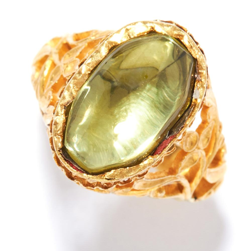 ANTIQUE PERIDOT RING in high carat yellow gold, set with a cabochon peridot in open scrolling gallery, unmarked, size M / 6, 7.50g.