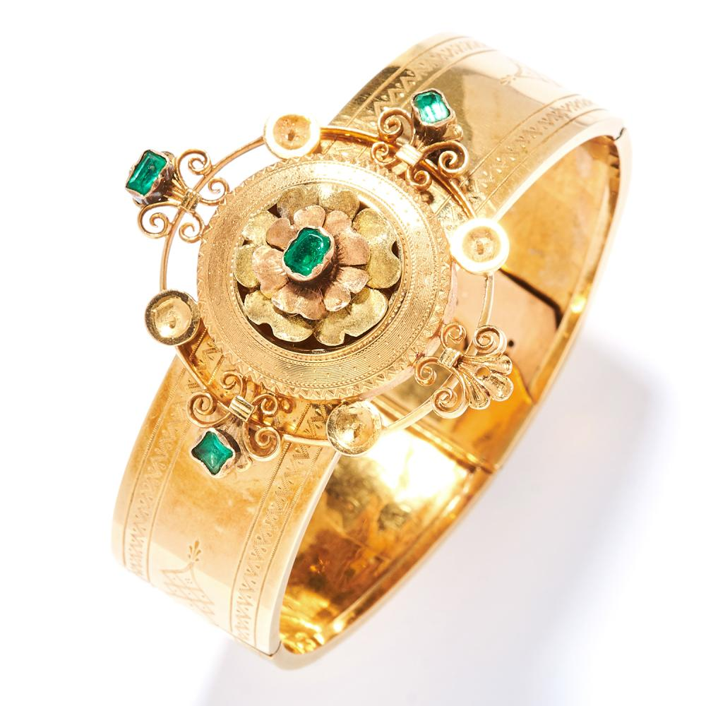 ANTIQUE EMERALD BANGLE, 19TH CENTURY in high carat yellow gold, the band with engraved decoration, with applied jewelled motif set with emeralds, unmarked, inner diameter 5.5cm, 23.2g.