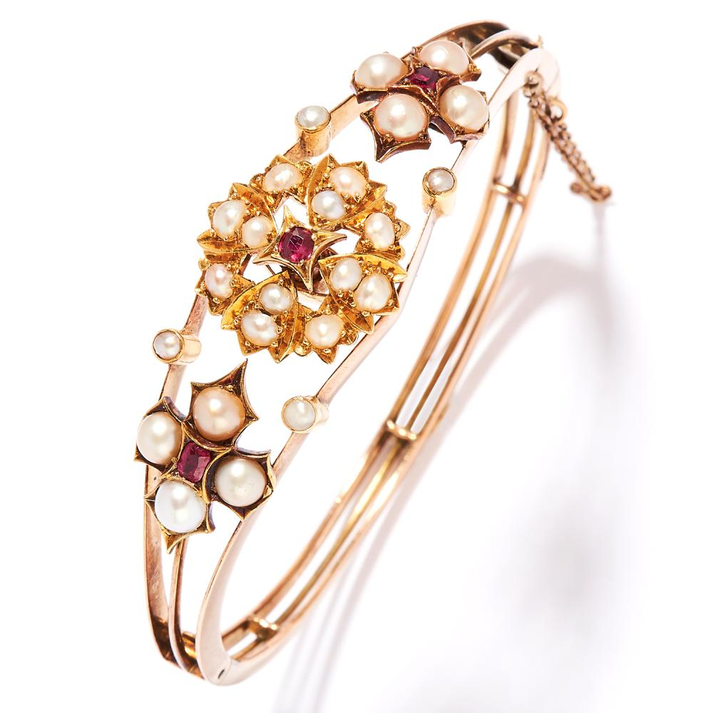 ANTIQUE PEARL AND RUBY BANGLE in 18ct yellow gold, the split, openwork design set with ruby and pearl clusters, stamped 18ct, inner diameter 5.7cm, 20.8g.