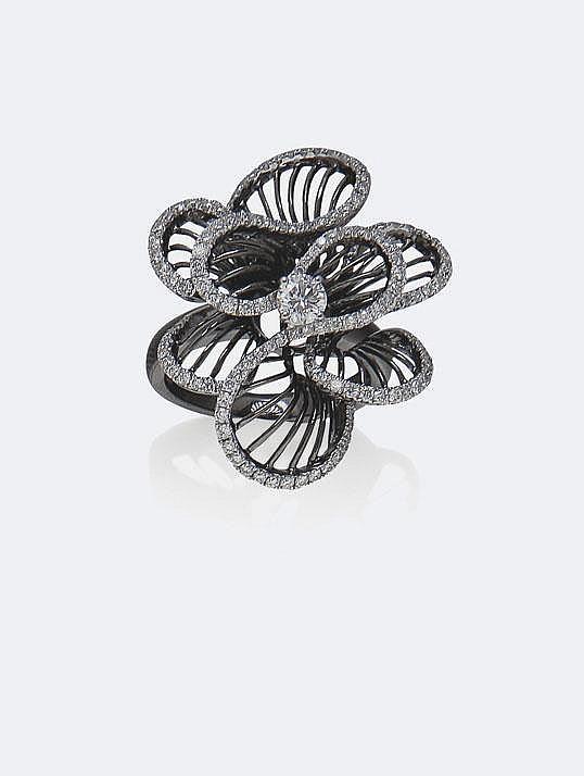 BAGUE dessinant huit pétales à rayures d'or noirci , bordés de diamants autour d'un brillant central, total : 3,30 carats environ. Taille : 53 - Poids : 9,49 g brut.