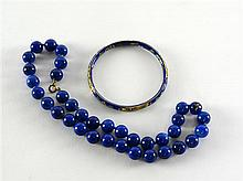 Lapis lazuli bead necklace with gold clasp, circa 1900, and a cloisonne bangle with floral decoration