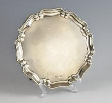 George V silver salver, on four scroll feet with s