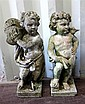 Two composite stone putti, one playing a tambourine, the other with a bird on his shoulder, on square bases