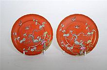 † Pair of Chinese coral ground small saucer dishes, each decorated with birds flying above prunus.