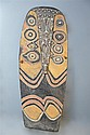 † New Guinea , Mid Ramu River area a large ceremonial shield , carved in low relief, with stylised face and eye forms