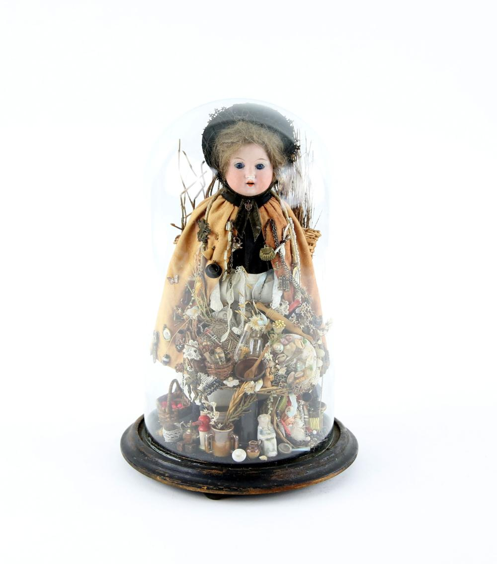 Early 20th century peddler doll under a glass dome