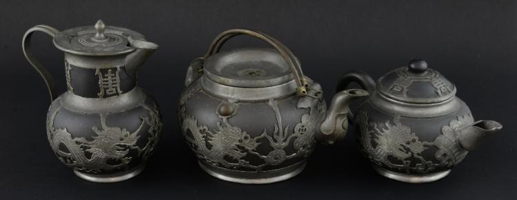 Three Chinese pottery pewter overlaid teapots, wit