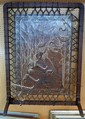 Arts and Crafts embossed fire screen on an oak surround, decorated with flowers and gilt highlights, stamped Finningans.