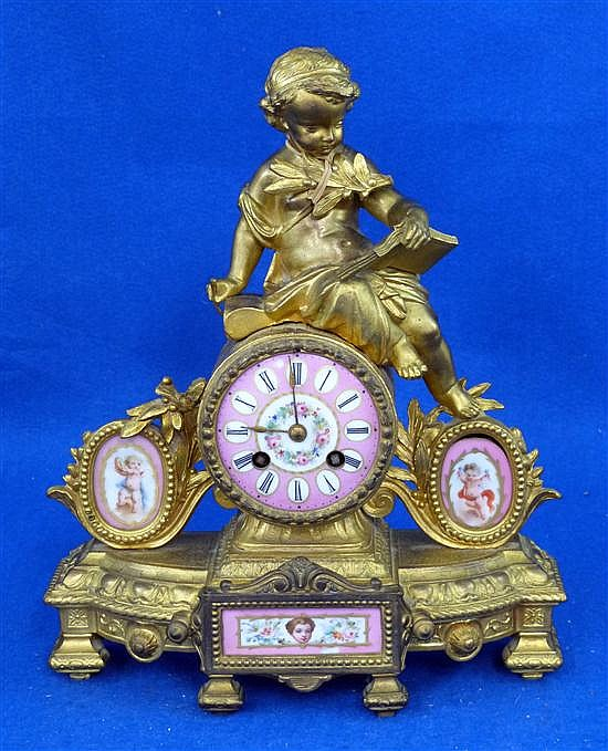 Late 19th century French gilt metal and porcelain mantel clock decorated with a cherub, floral porcelain mounts, striking on bell