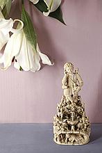 Jésus Bon Pasteur en ivoire sculpté en ronde-bosse. Entouré de moutons et assis sur un rocher, l'Enfant est endormi, un agneau sur une épaule, un autre tenu par la main gauche ; il est revêtu d'une tunique en peau de mouton ceinturée, avec besace en