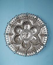 Grand plat en argent repoussé et ciselé. Le bassin est orné de l'Adamastor dans un entourage de style manuelin de cordages stylisés polylobés figurant des caravelles. L'aile est ornée des blasons du Portugal et de sphères armillaires surmonté de la