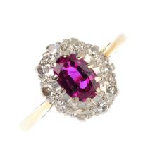 A synthetic ruby and diamond cluster ring. The oval-shape synthetic ruby, w