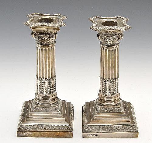 A pair of Edwardian silver mounted Corinthian column candlesticks.