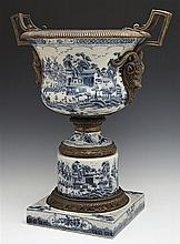 Chinese Bronze Mounted Porcelain Campana Form Urn, with ram's head handles, the sides and socle support with