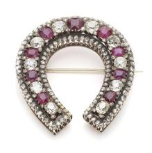 A ruby and diamond brooch of horseshoe design