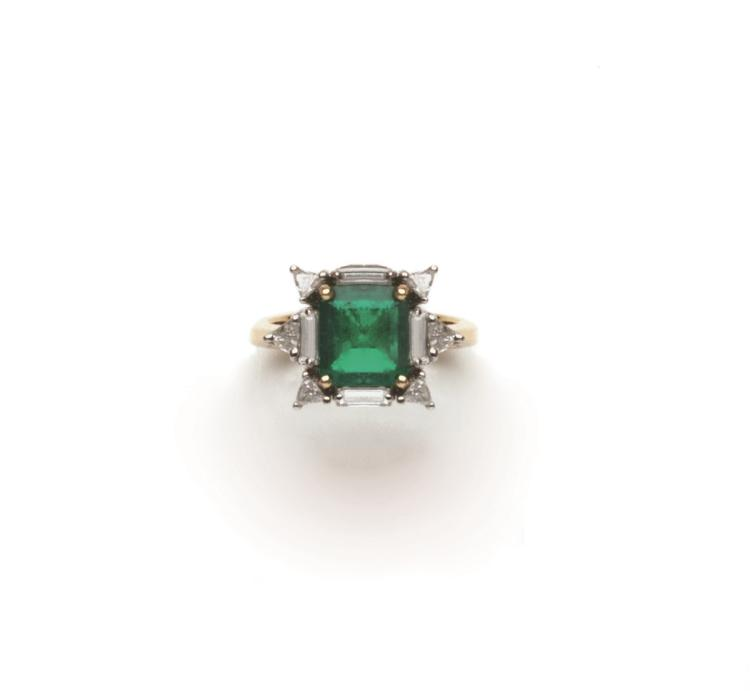 An emerald and diamond ring set with a step-cut emerald