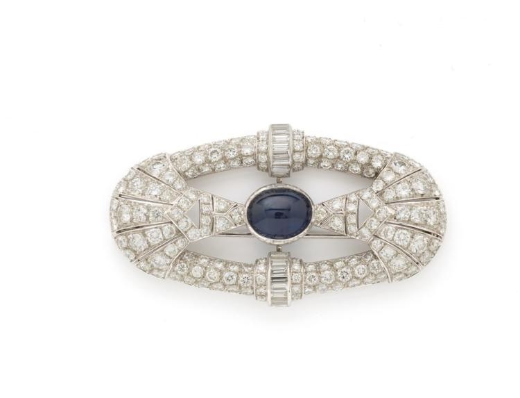 A deco sapphire and diamond brooch, set with a cabochon sapphire weighing approximately 13.00 carats
