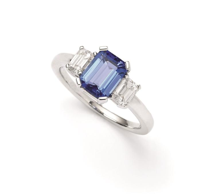 An 18ct gold tanzanite and diamond ring, the emerald cut tanzanite set between emerald-cut diamond surround
