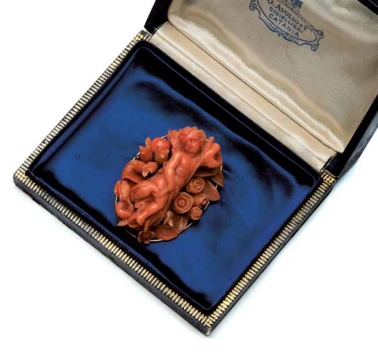 A 19th century coral brooch, set with carved coral depicting a little angel and flowers
