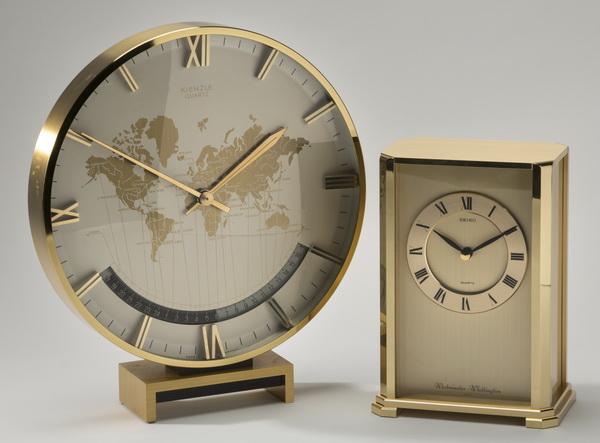 Two brass quartz clocks, one with world time